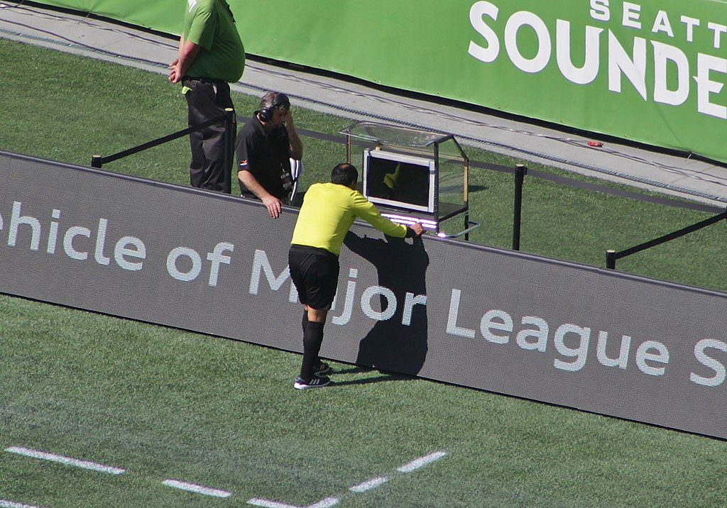 Referee Baldomero Toledo consults the video assistant referee during a Major League Soccer match between Seattle Sounders FC and Sporting Kansas City (Credit: Wikimedia Commons/ Sounder Bruce)
