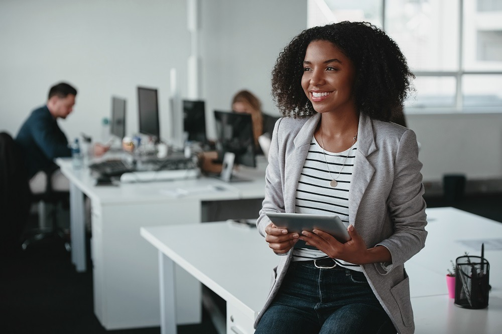 Happy thoughtful young businesswoman with digital tablet in hand smiling and looking away in front of colleague at background