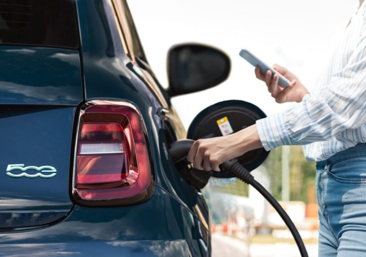 Young adult woman charging electric car, using smartphone